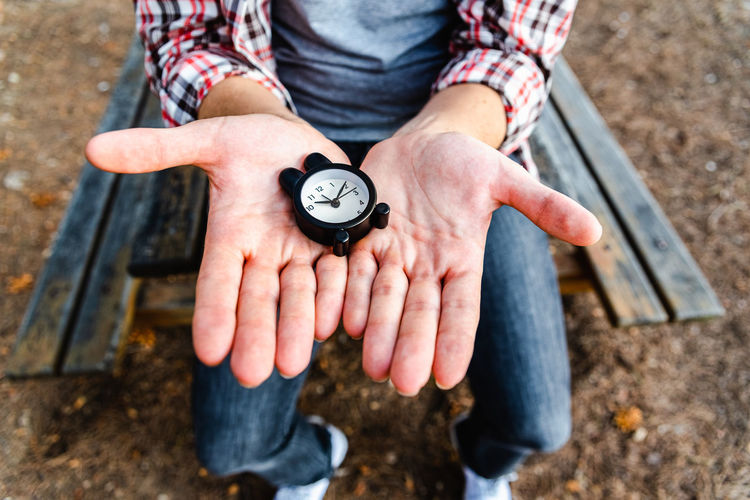 Midsection of person holding clock