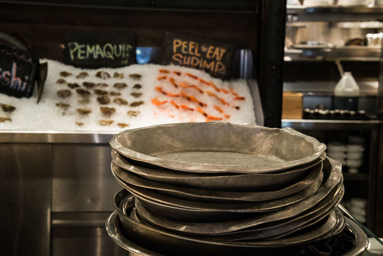Stack Of Pewter Dishes On Counter In Commercial Kitchen At Restaurant