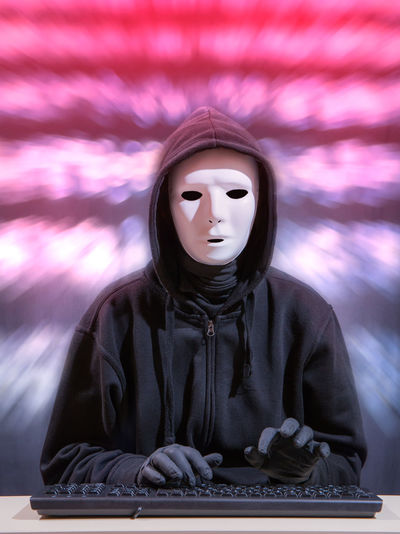 Portrait of woman wearing mask while typing on keyboard against blurred background