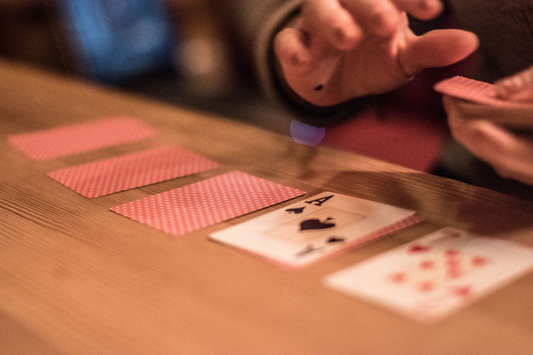 Close-up of hands holding playing cards on table