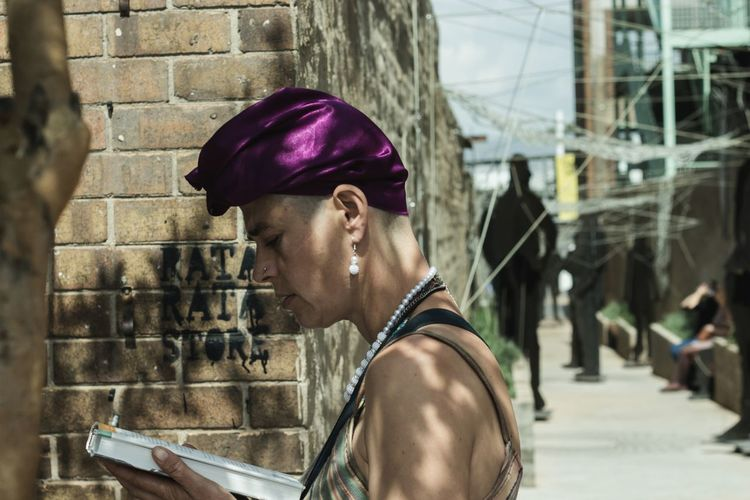 Side view of woman reading book by brick wall in city
