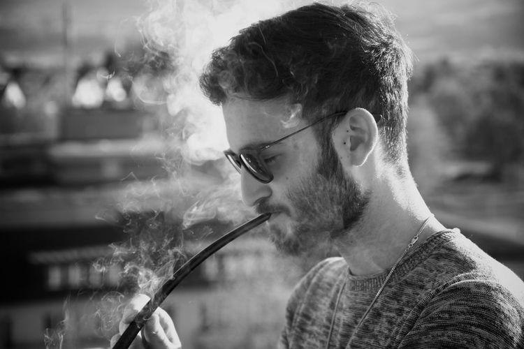 Side View Of Man Smoking Pipe At City