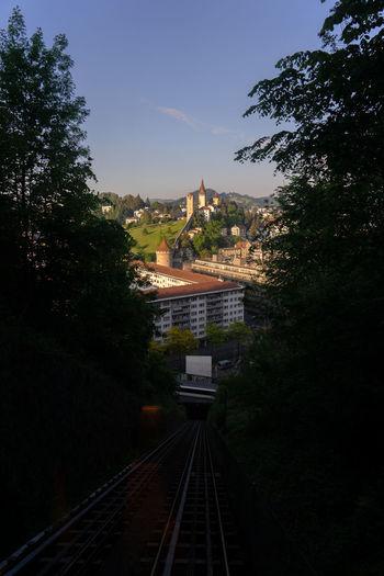 Train passing through city against sky