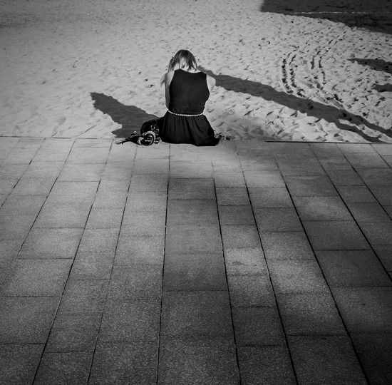 Rear view of woman in black dress sitting at beach