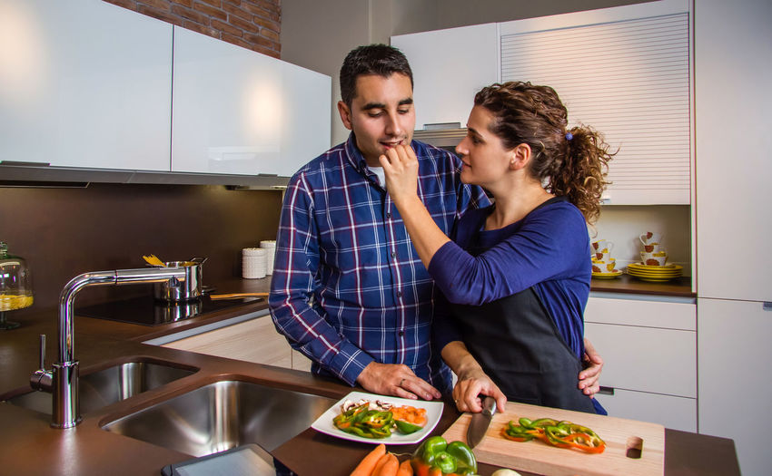 Woman giving food to man in kitchen at home