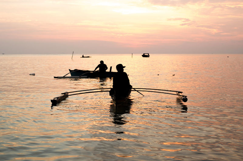 sunrise with fsherman. Water Sky Sunset Sea Nautical Vessel Transportation Waterfront Scenics - Nature Men Beauty In Nature Mode Of Transportation Silhouette Orange Color Nature Horizon Over Water Two People Tranquility People Reflection Outdoors Rowboat Fisherman