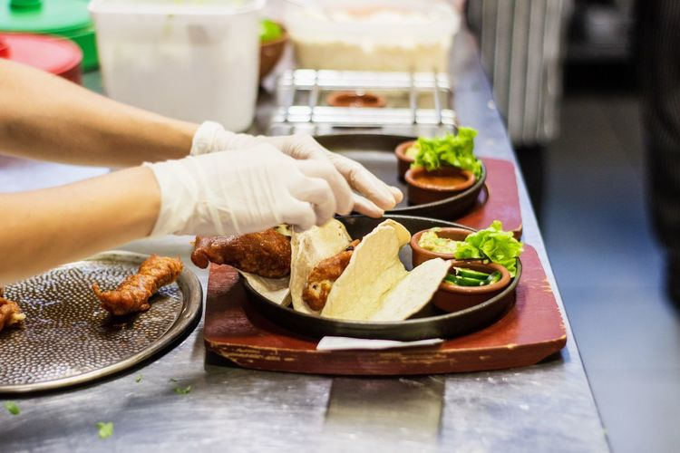 Midsection of man preparing food in plate on table