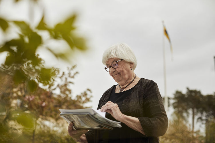 Portrait of woman holding paper outdoors