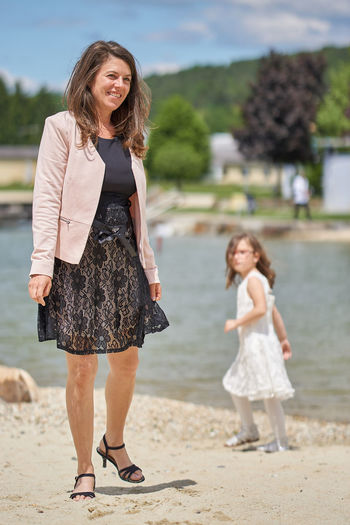 Happy Woman With Girl Standing By Lake On Sunny Day