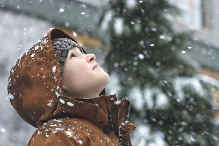 Boy looking up during snowy winter