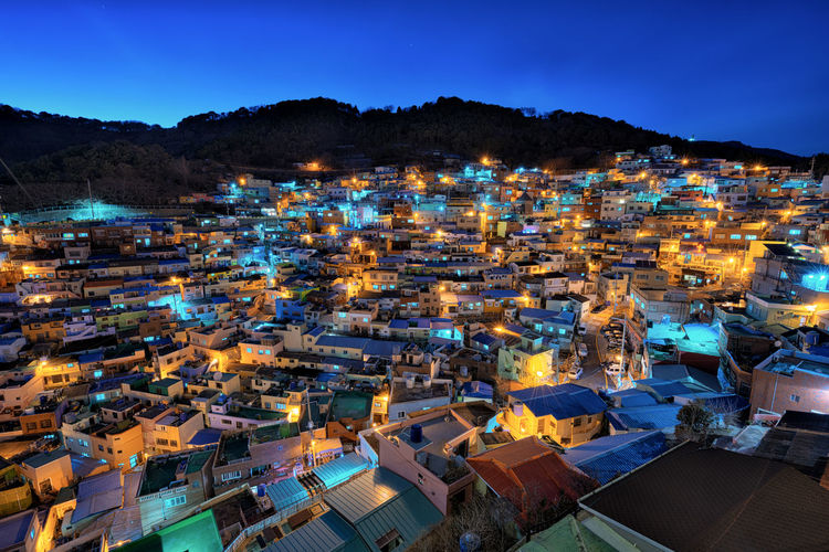 Aerial view of illuminated houses in town against sky at night