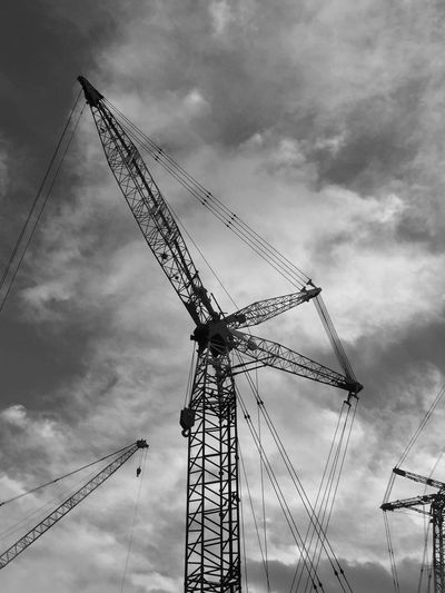 Low angle view of silhouette cranes against cloudy sky