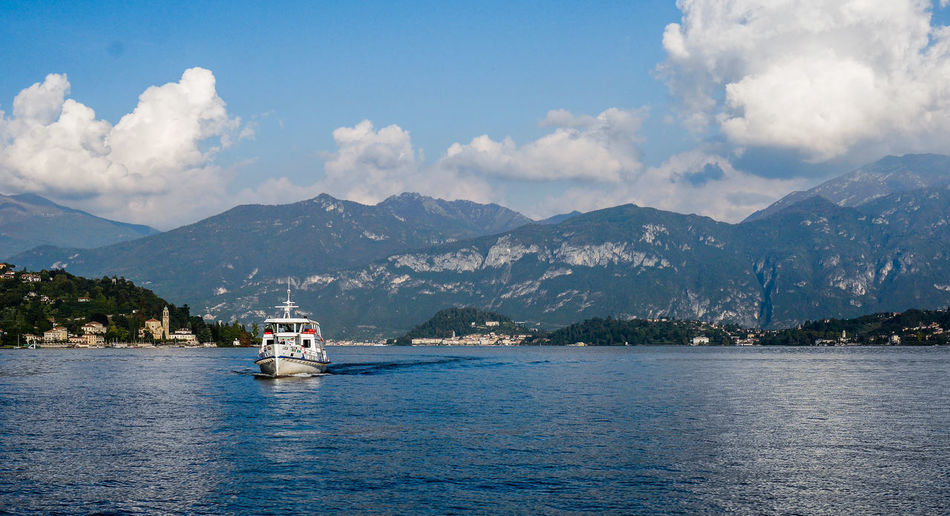 Boat On Lake Como By Mountains Against Cloudy Sky