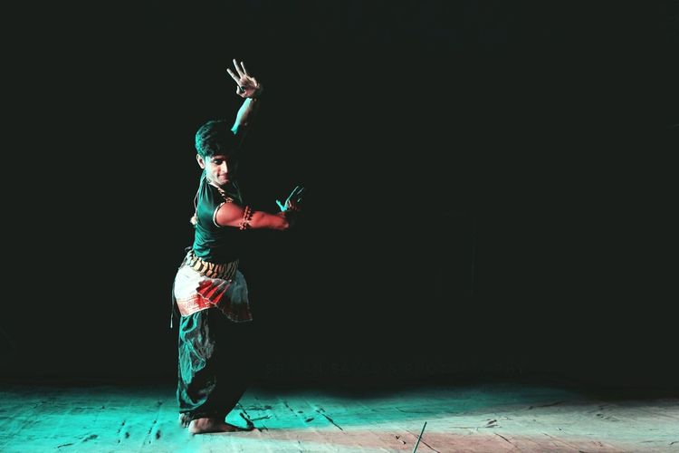 Full length of man wearing traditional clothing while dancing on stage
