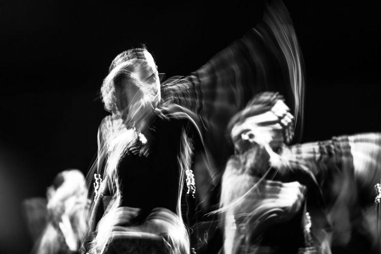 Blurred motion of dancer dancing against black background