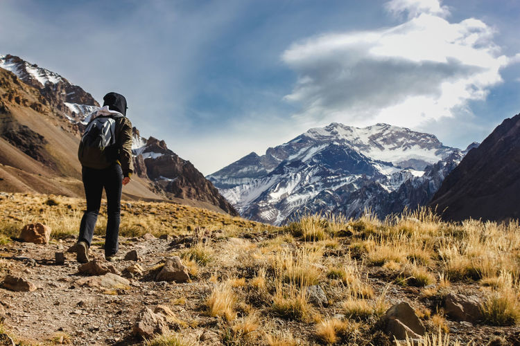 Rear view of hiker walking on mountain against sky