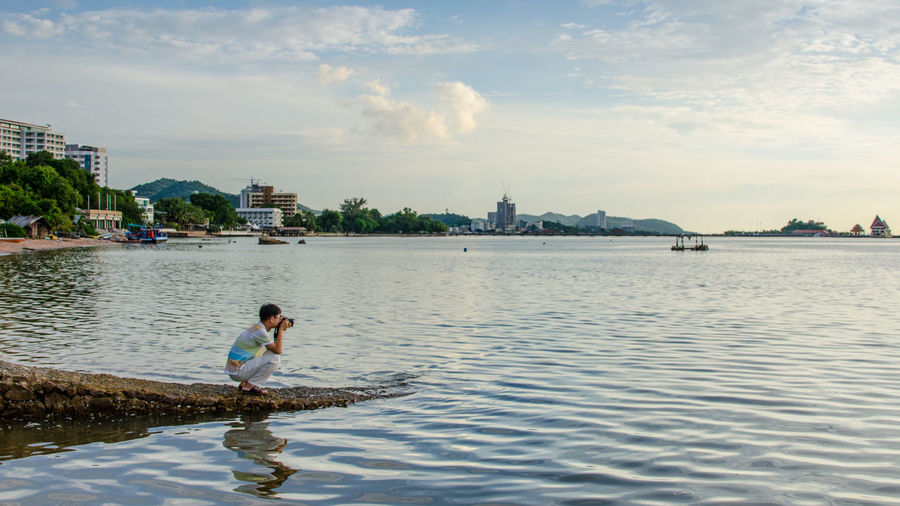 Man photographing river in city