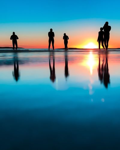 Silhouette people at swimming pool against sky during sunset