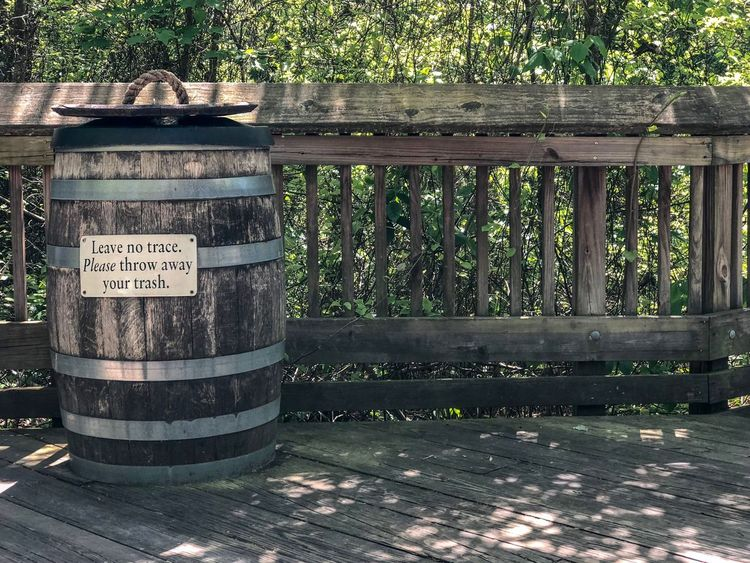 Leave no trace only foot steps Trash Trash Can Text Communication Western Script Day Nature Wood - Material No People Sunlight Non-western Script Sign Script Plant Barrier Information Outdoors Safety Fence Information Sign Tree Boundary