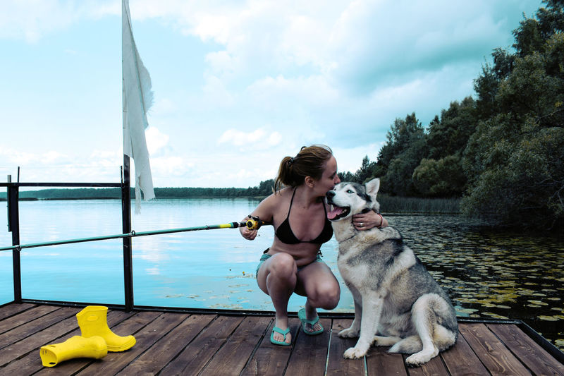 Woman with husky dog sitting on a pier against the sky