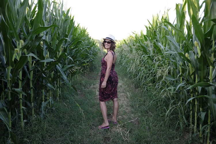 Portrait of smiling woman standing on field amidst cereal plants