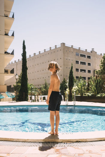 Full length of man standing by swimming pool against sky