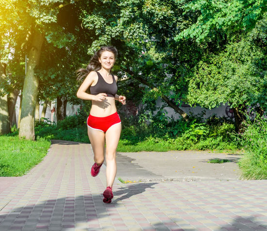Brunette girl in red shorts running along the path in the park Beautiful Woman Beauty Clothing Day Footpath Full Length Hairstyle Leisure Activity Lifestyles Looking At Camera Nature One Person Outdoors Plant Portrait Real People Shorts Teenager Tree Women Young Adult Young Women