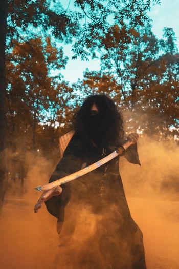 Warrior holding sword standing outdoors