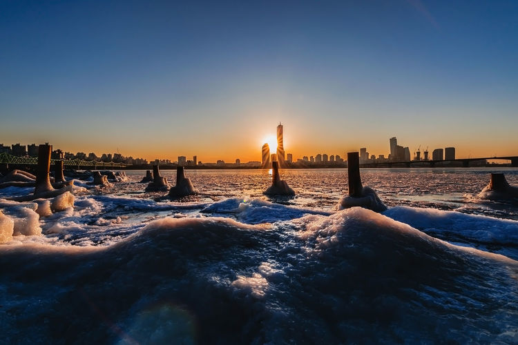 Evening sunset at the Han River in winter South Korea Architecture Beauty In Nature Building Exterior Built Structure City Cityscape Clear Sky Cold Temperature Copy Space Land Nature No People Office Building Exterior Outdoors Scenics - Nature Sea Sky Snow Sunset Travel Destinations Water Winter
