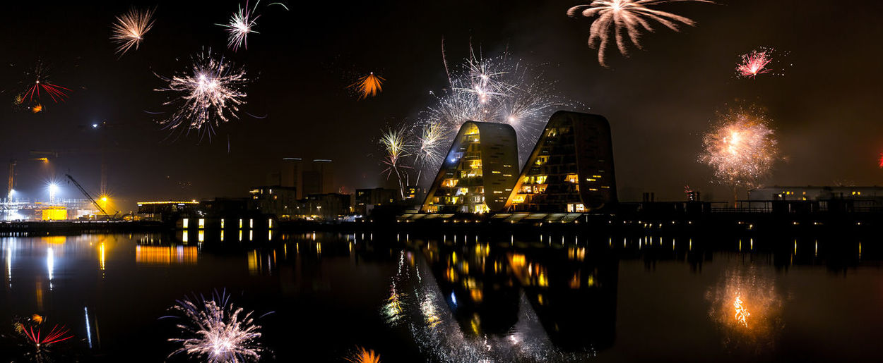 Reflection of illuminated buildings and fireworks in river at vejle