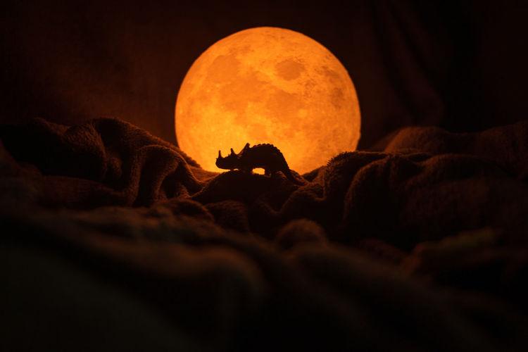 Close-up of orange lights against sky at night