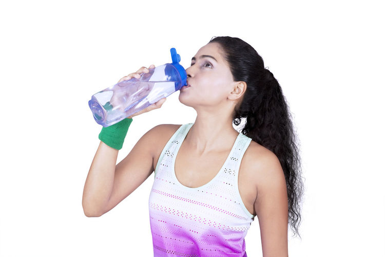Mid Adult Woman Drinking Water While Standing Against White Background