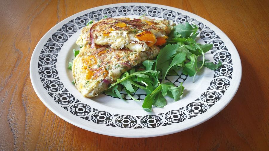 High Angle View Of Omelet With Arugula Leaves In Plate