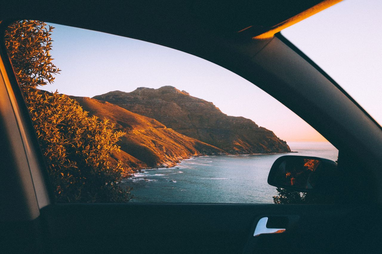 Mountain in sea seen through car window