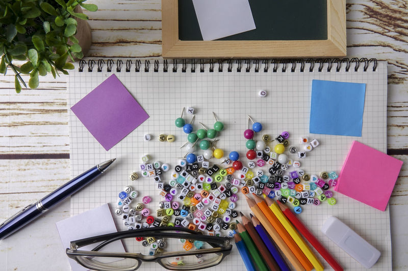 Directly above shot of alphabet beads with school supplies on table