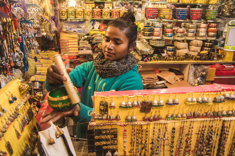 High angle view of young woman buying tibetan singing bowl in store