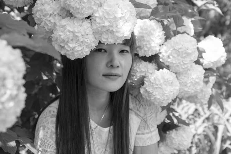 Portrait Of Young Woman Sitting Amidst Hydrangea Flowers