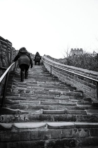 Climbing the Great Wall Great Wall of China blackandwhite monochrome Winter climbing Going the Great Wall Of China Blackandwhite Monochrome Winter Climbing Journey Up Notforthefaintofheart Steps Rear View Walking Railing Sky Be Brave Stairway