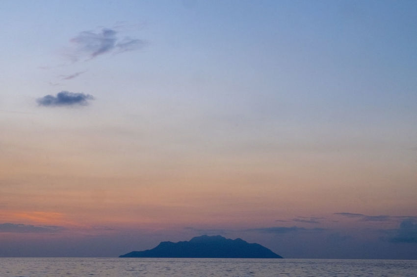 ALONE AT SEA Beauty In Nature Cloud - Sky Horizon Horizon Over Water Idyllic Mountain Nature No People Non-urban Scene Orange Color Outdoors Scenics - Nature Sea Sky Sunset Tranquil Scene Tranquility Water Waterfront