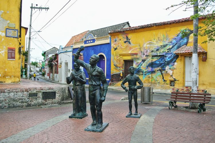 Statue on footpath by street against buildings in city