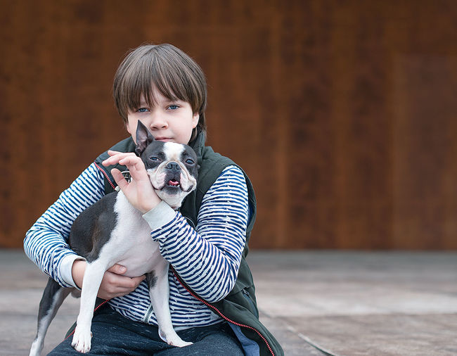 Portrait of boy holding dog sitting outdoors