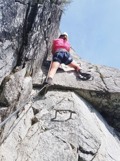 Low angle view of woman climbing on rock