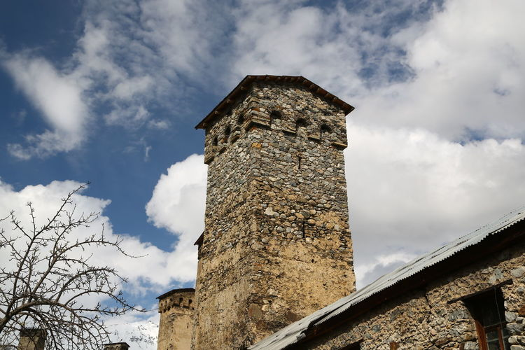 Georgia Mestia/town In Svaneti/Georgia Sky Architecture Built Structure Cloud - Sky Low Angle View Building Exterior Nature No People Day History Building The Past Old Outdoors Tower Wall Bare Tree Stone Wall Plant Tree