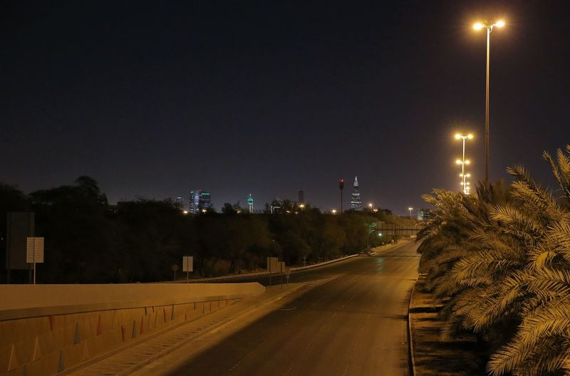 Road by illuminated city against sky at night