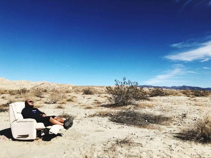 Men Sitting In Desert Against Blue Sky