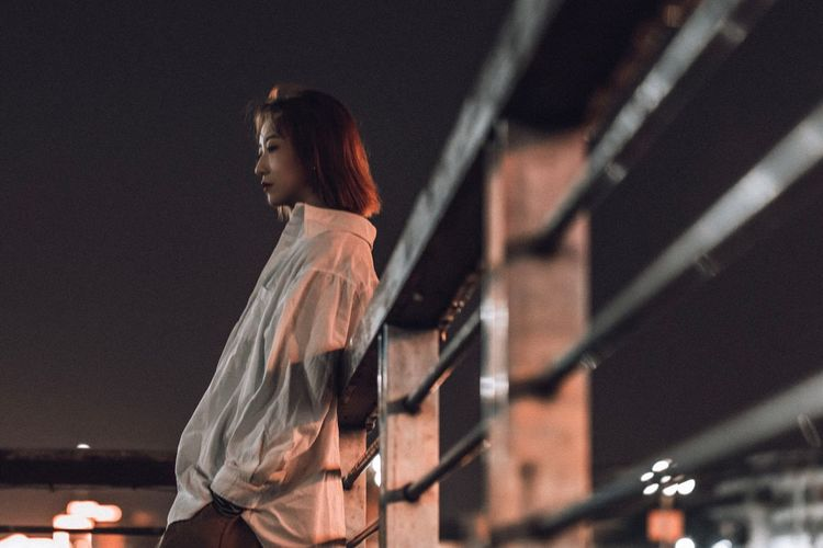 Side view of woman looking at night