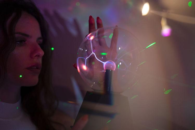 Portrait of woman holding illuminated lights