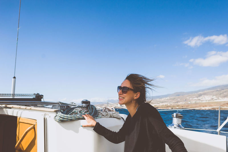 Happy woman with sunglasses on boat in sea against sky