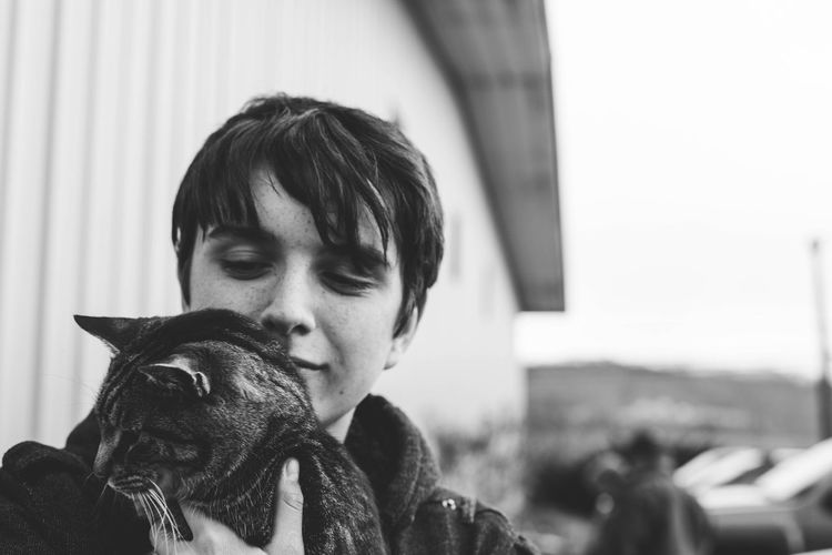 Cat whisperer. Headshot Real People Lifestyles One Person One Animal Close-up Portrait Domestic Animals Pets Young Adult Cat Boy Teenager Blackandwhite Candid Candid Photography Candid Portraits
