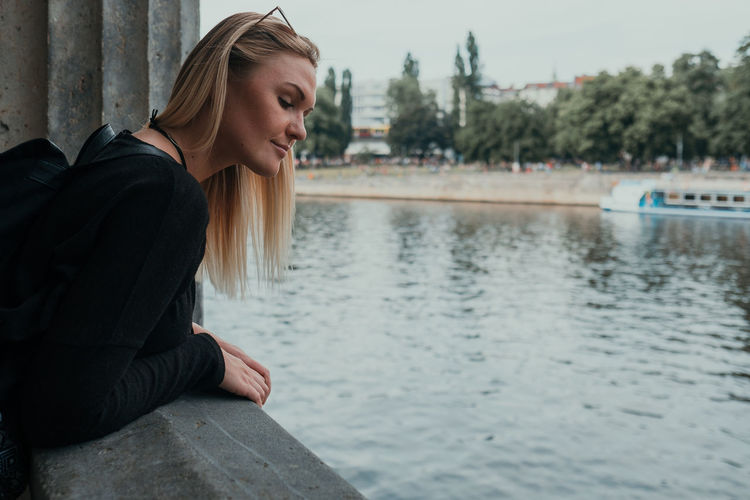 Young woman looking away while sitting on lake